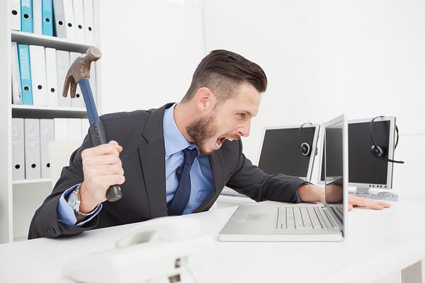 Angry businessman holding hammer over laptop in his office