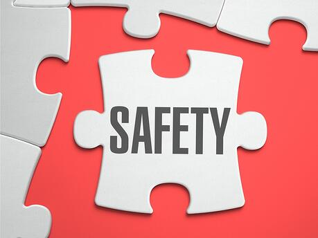 Safety - Text on Puzzle on the Place of Missing Pieces. Scarlett Background. Close-up. 3d Illustration..jpeg